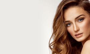 Female With Wavy Light Brown Hair and Blue Eyes Looking Over Bare Shoulder - Mobile Homepage
