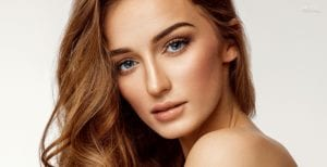 Female With Wavy Light Brown Hair and Blue Eyes Looking Over Bare Shoulder - Tablet Homepage