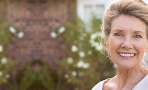 Mature Female Smiling Outdoors In Front of Rose Garden - Dental Implants Homepage for Mobile