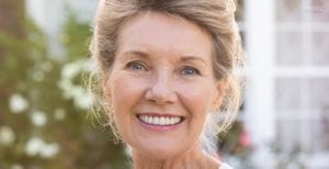 Mature Female Smiling Outdoors In Front of Rose Garden - Dental Implants Homepage for Tablet