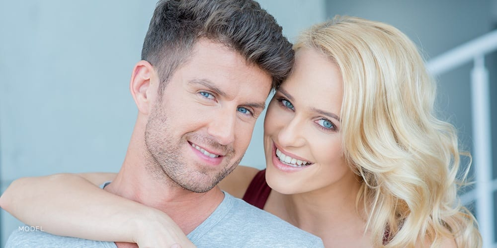 Blond Female Smiling At Camera With One Arm Over Caucasian Male With Blue Eyes