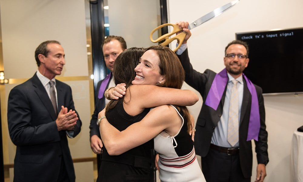 Dr Vigliante Holding Giant Scissors At Ribon Cutting Ceremony With Two Women Hugging In Foreground